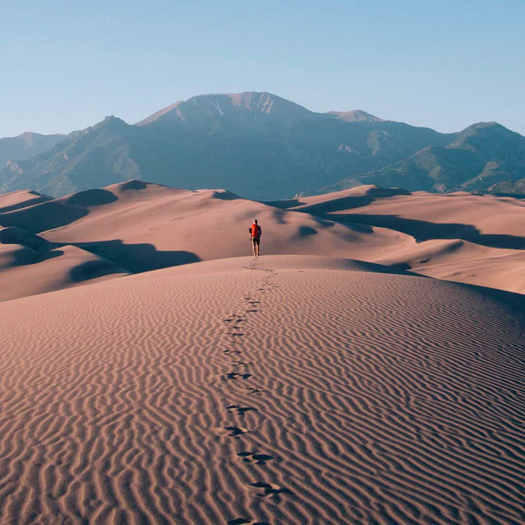 person walking in desert